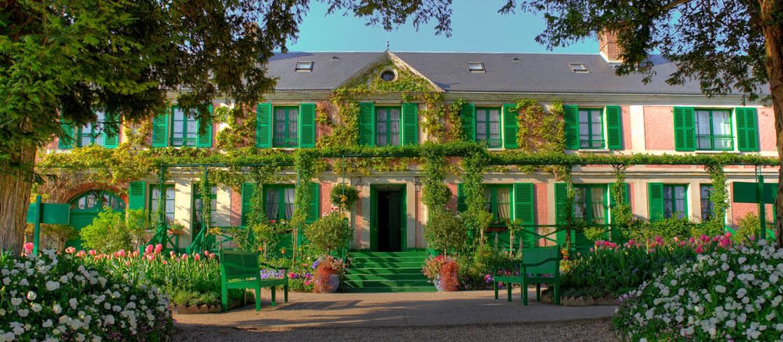 Pintada de rosa, bordeada de flores y de árboles, la casa del maestro del impresionismo, Claude Monet, rebosa encanto.