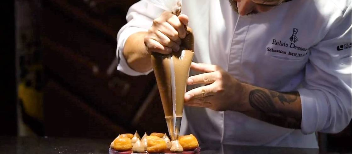 Sébastien Bouillet, the Lyonnais chocolatier-pastry chef creates one of his gourmet desserts, made with cream and babas au rhum.